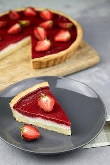 Кусок клубничного пирога со свежими ягодами на серой тарелке на каменном столе