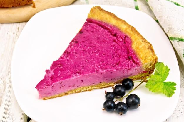 접시에 검은 건포도와 달콤한 케이크 조각, 나무 판의 배경에 대해 냅킨