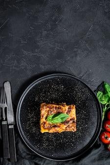 おいしいホットラザニアの作品。伝統的なイタリア料理。黒の背景。上面図。テキストのためのスペース