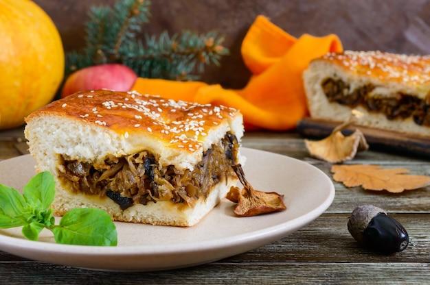 Кусок вкусного пирога с капустой и лесными грибами