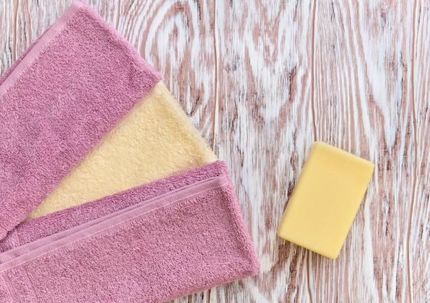 木製の背景にトイレの石鹸とタオルの一部