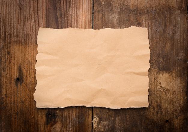 Кусок рваной бумаги на старом деревянном столе гранж