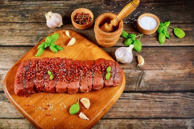 Кусок сырой сырой говядины со специями на деревянной доске