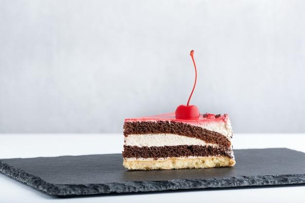 黒のプレートにマラスキーノチェリーを添えた白とチョコレートのスポンジケーキ。ケーキの側面図。