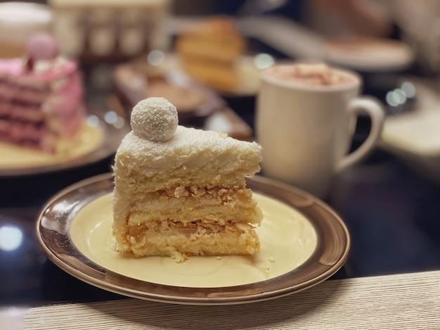 Кусок белого торта с бисквитом, кокосовой стружкой и украшением поверх торта в виде шара на тарелке в ресторане.