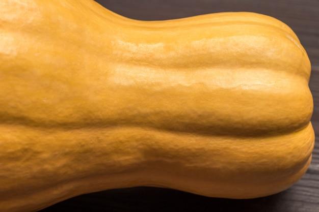 黄色いカボチャのかけら。閉じる。木製の背景。