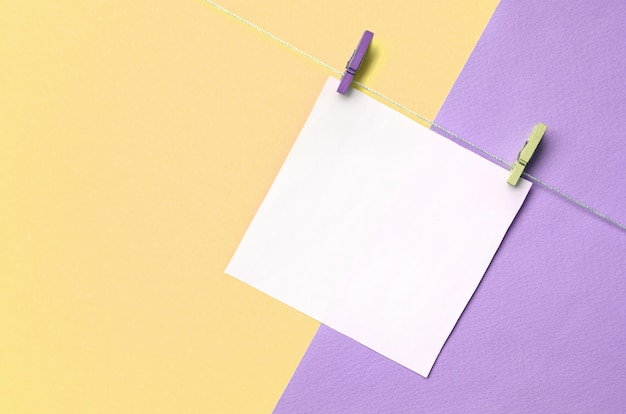 A piece of paper is hanging on a rope with pegs on texture of fashion pastel yellow and violet colors