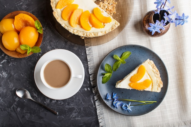 A piece of peach cheesecake on a blue ceramic plate with blue flowers and a cup of coffee on black