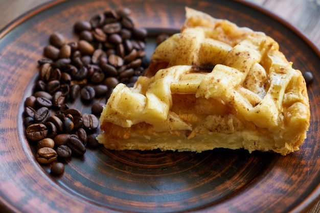 Piece of peach pie on a plate with coffee beans close up