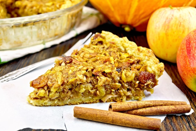 Piece of pie with apples, pumpkin, raisins and nuts on parchment, cinnamon on the background of a wooden board