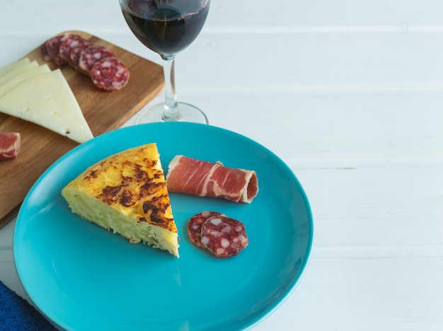 Piece of potato omelette with ham and sausage on a blue plate with a glass of wine on a white table.