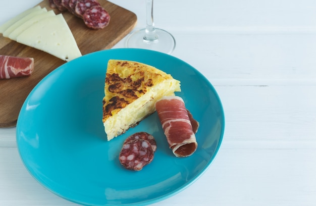 Piece of potato omelette with ham and sausage on a blue plate