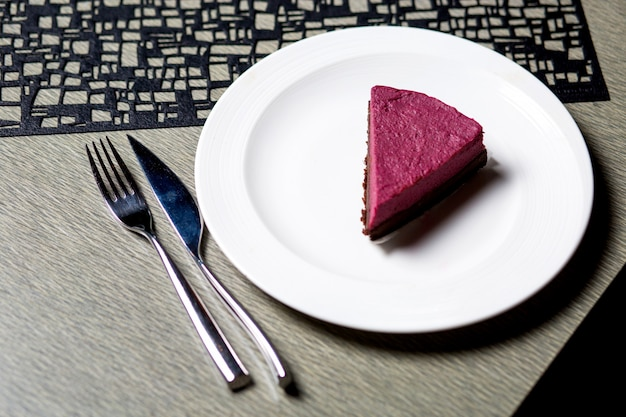 A piece of raspberry cheesecake in white plate served on the table