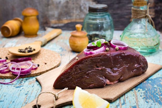 A piece of raw beef liver on a cutting board, onion, lemon and spices for cooking