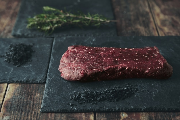 Piece of raw meat on black stone pad near black volcanic salt and rosemary herb and spices