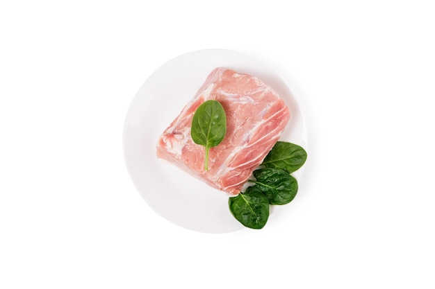 Piece of raw pork meat with spinach on a white ceramic plate.