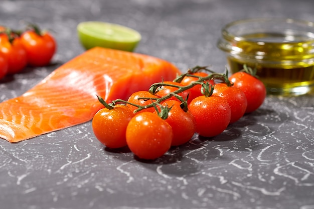 A piece of salmon on a gray background, tomatoes, dill, olive oil, lemon. selective focus