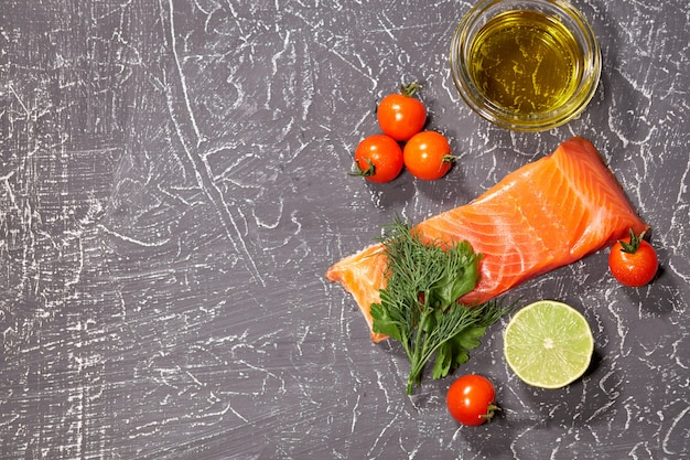 A piece of salmon on a gray background, tomatoes, dill, olive oil, lemon.