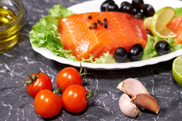 A piece of salmon on a white plate with olives and lemon, on a gray background.