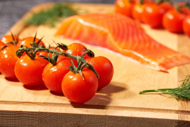 A piece of salmon on a wooden board, tomatoes and dill. selective focus