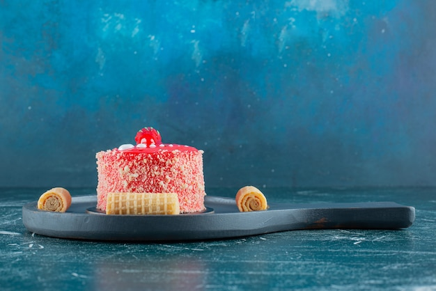Piece of strawberry cake and waffle rolls on black cutting board.