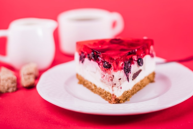 A piece of strawberry jelly cake on white plate against red backdrop