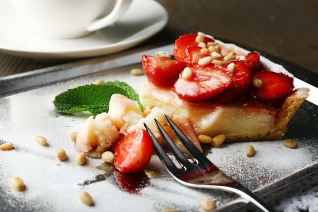 Piece of strawberry tart on  tray, on rustic wooden background