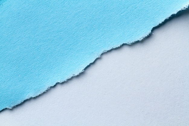 A piece of torn blue paper. note paper strips for text or message stuck on a blue background