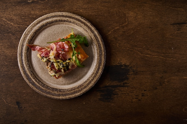Piece of traditional italian roman pizza lies on rustic ceramic plate on brown wooden background