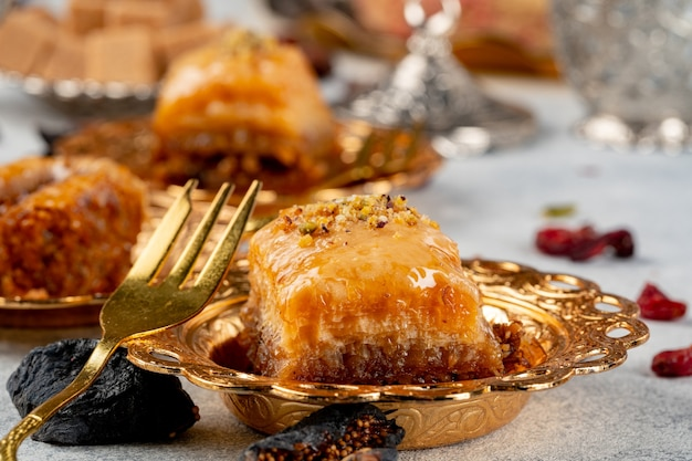 Piece of turkish baklava in golden arabic plate