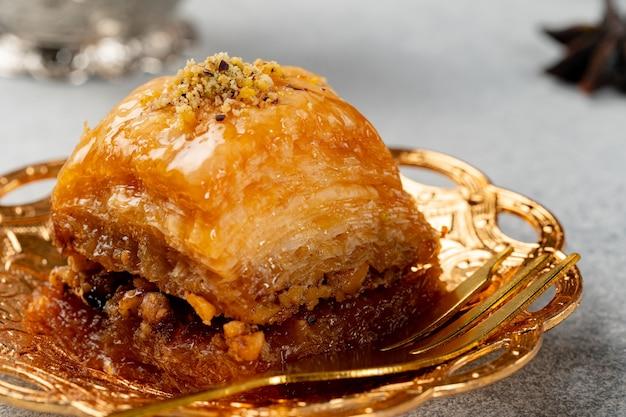 Piece of turkish baklava in golden arabic plate