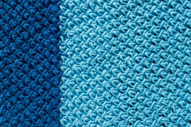Piece of two-color blue knitted fabric, background or texture. knitting yarn handmade