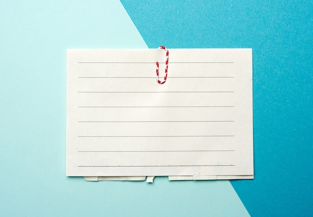 Piece of white paper in a line and a red paper clip on a blue background