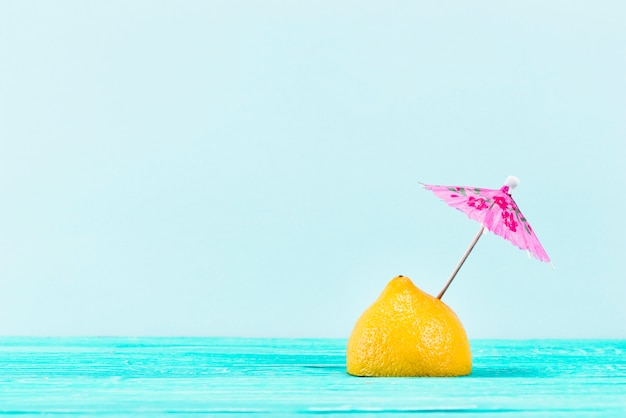 Piece of yellow lemon with pink umbrella on top on blue background