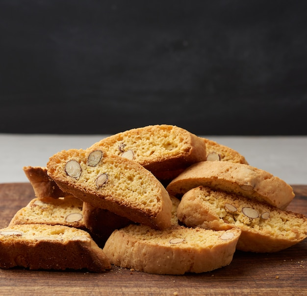 Pieces of baked italian christmas biscotti cookies on a brown wooden board