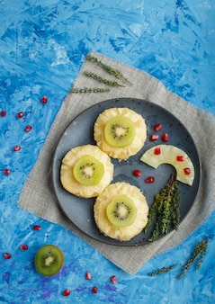 Pieces of baked pork with pineapple, cheese and kiwi on blue