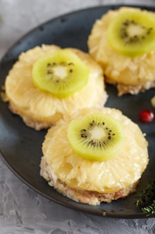 Pieces of baked pork with pineapple, cheese and kiwi on gray background.