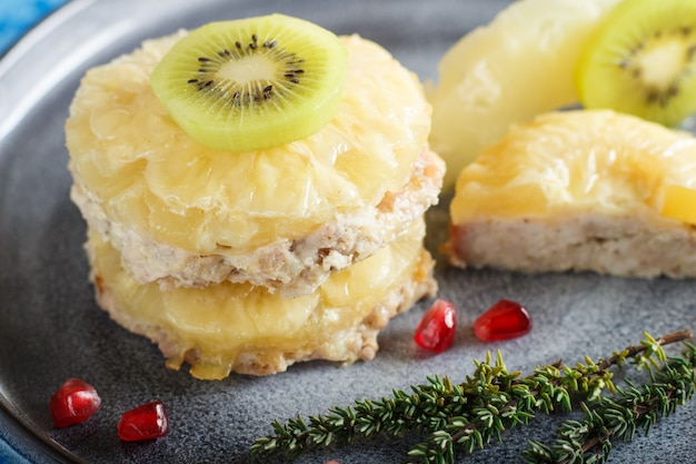 Pieces of baked pork with pineapple, cheese and kiwi on gray plate and blue background.