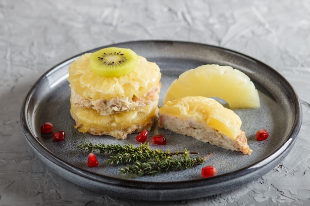 Pieces of baked pork with pineapple, cheese and kiwi on gray plate.