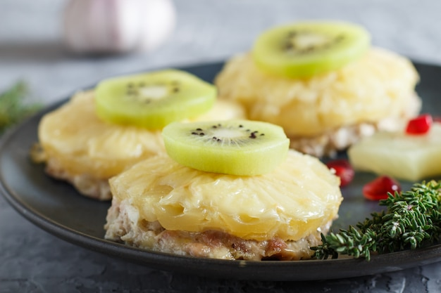 Pieces of baked pork with pineapple, cheese and kiwi on gray