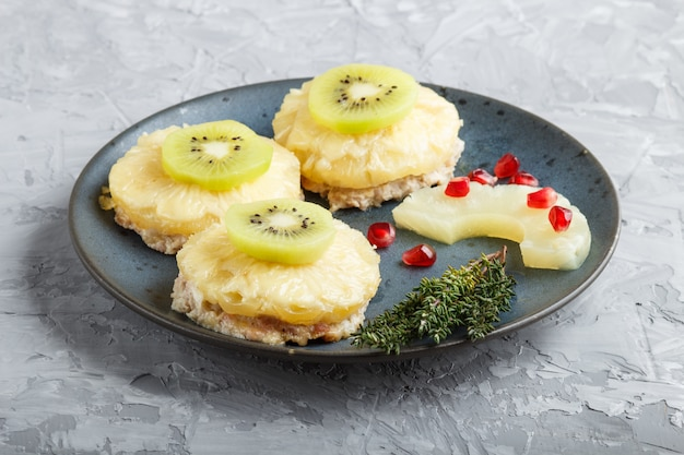 Pieces of baked pork with pineapple, cheese and kiwi