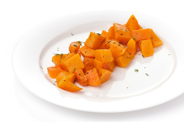 Pieces of baked pumpkin in white plate on white background