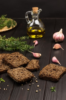 Pieces of black bread, sprigs of thyme, oil in glass bottle and garlic on table. top view