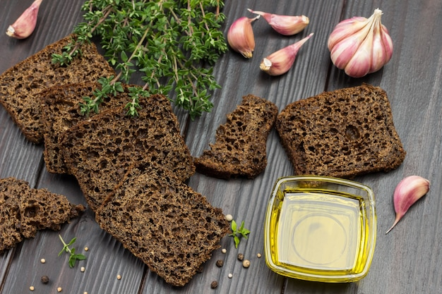 Pieces of black bread, thyme sprigs, butter in glass bowl and garlic on table. top view