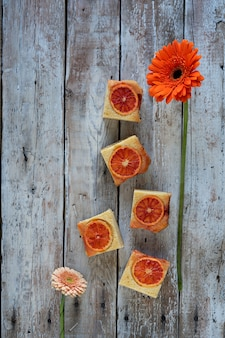 A pieces of blood orange cake and red flower on wooden background