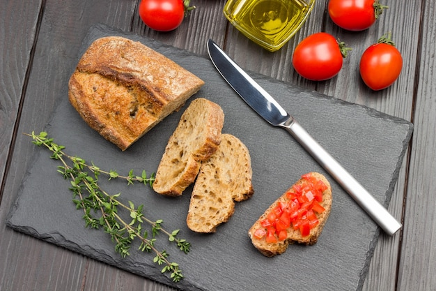 Pieces of bread and knife. sliced tomato sandwich