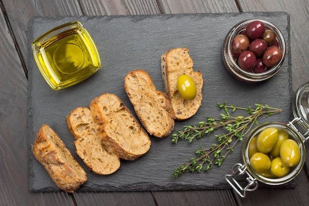 Pieces of bread, sprigs of thyme. jars of olives and glass bowl of oil. delicious snack and appetizer. flat lay.