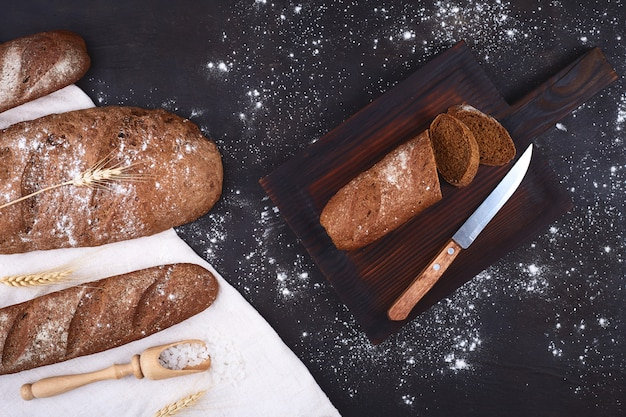 Pieces of bread with a knife, grain and spikelets. on dark rustic
