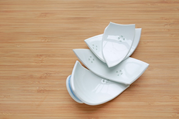 Pieces of broken ceramic bowl on wood background.
