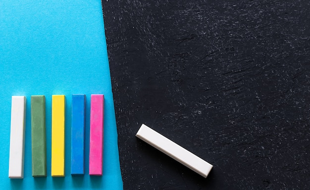 Pieces of chalk on the blackboard and blue background